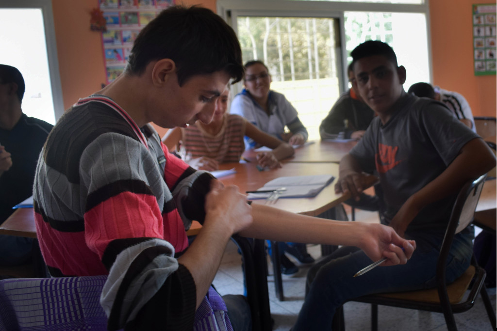 Zacaria, 17, mimes cutting his forearm while displaying a faint grid of previous scars. Depression and suicide are coming amongst children and adults with mental disabilities. Because of the social stigmas and shame surrounding this, these individuals often feel isolated and withdrawn from society. (Photo by Emma Hohenstein)