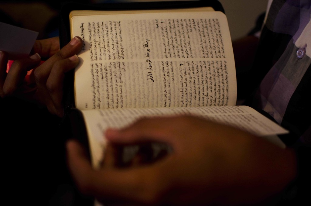 Eighteen-year-old Ishmael reads from the Bible. Some members of house churches disguise their Bibles in plastic bags or leather covers. (Photo by Julia Levine)