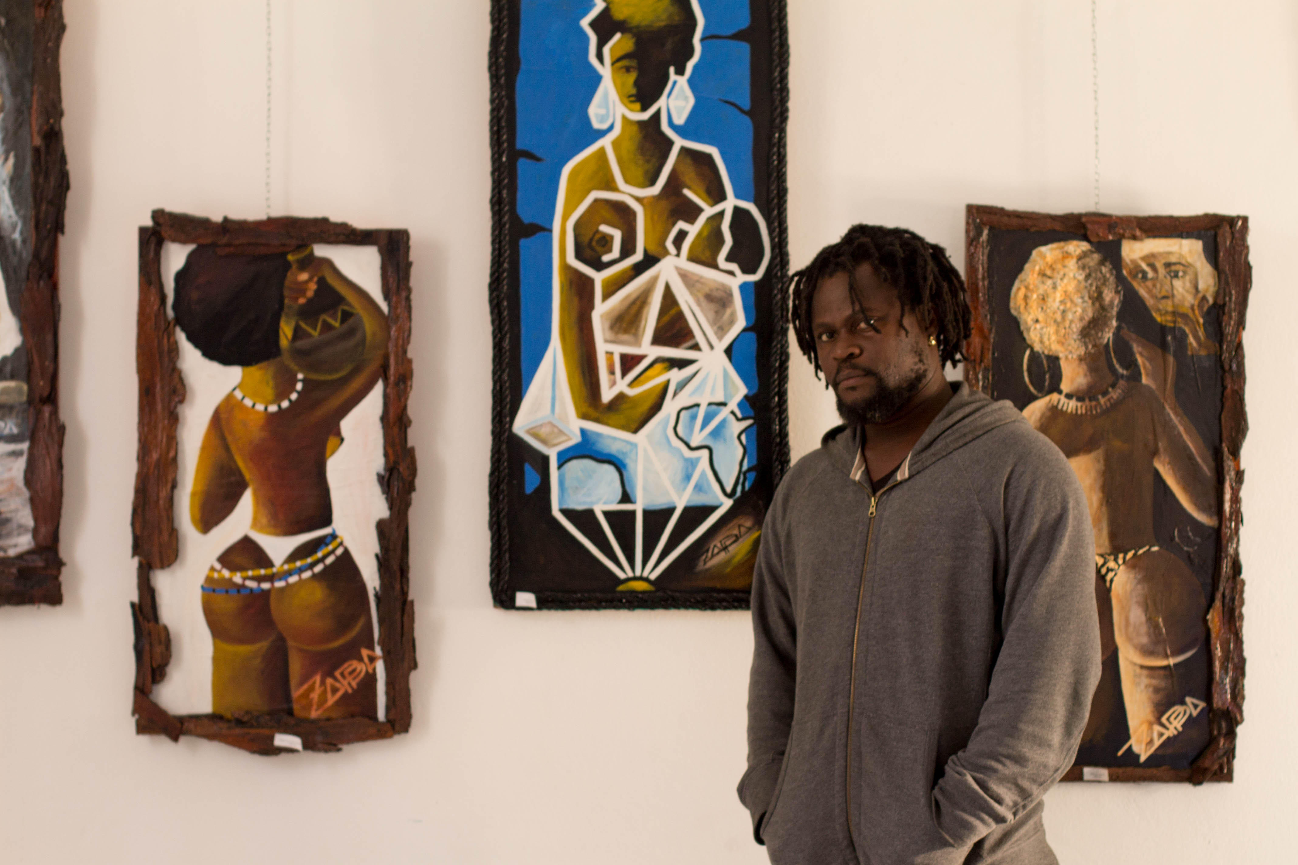 Zappa poses with three of his paintings that hang in the ACC's indoor art gallery. He calls himself a master of the African female form. His work is imbued with the spirit of Africa, and he often inserts symbols, like the outline of Africa, into his paintings. Photo by Allegra Thomas.