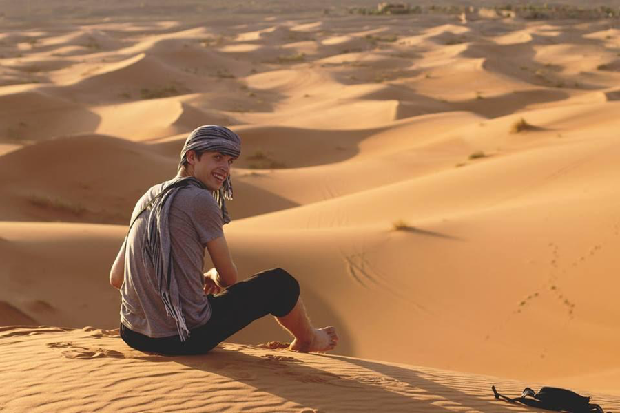 Simeon Lancaster of the Fall 2015 MOJ program sits atop sand dunes near Merzouga during the Southern Excursion. Photo courtesy of Simeon Lancaster.