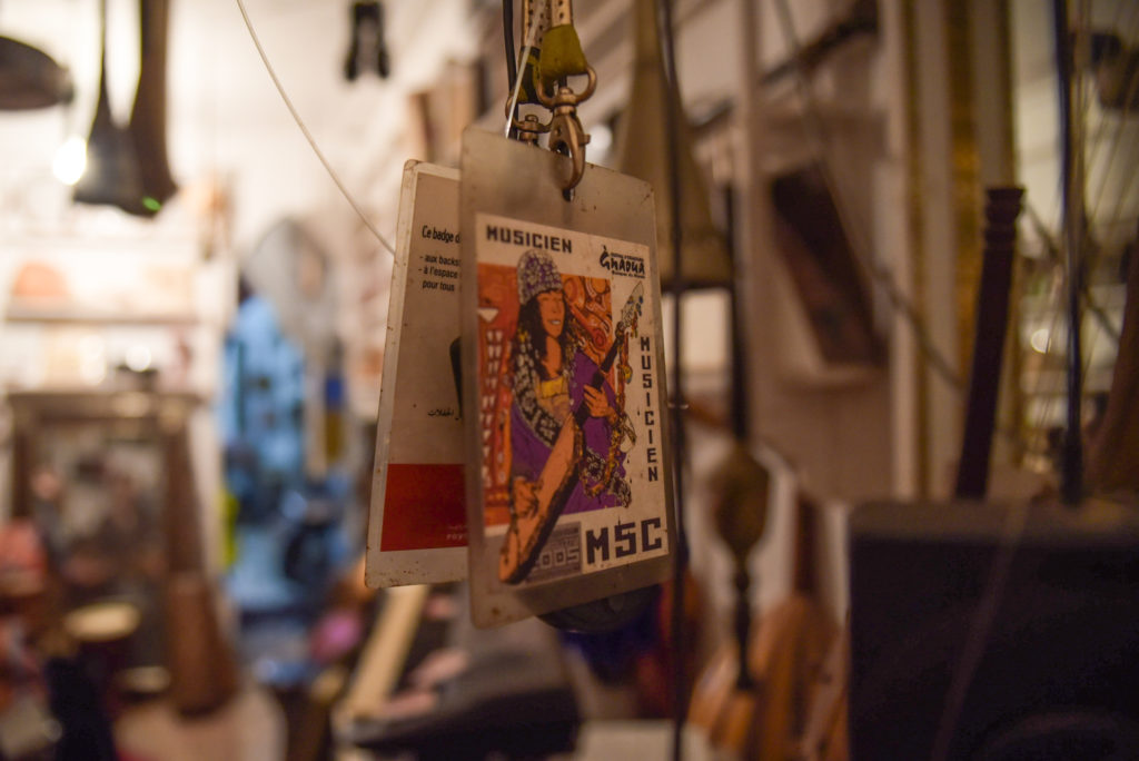 Two musician passes from previous Gnaoua World Music Festivals hang as a memento in the shop. Mustapha and his family and friends perform through Morocco in a 22-person band. Photo by Shirley Chan