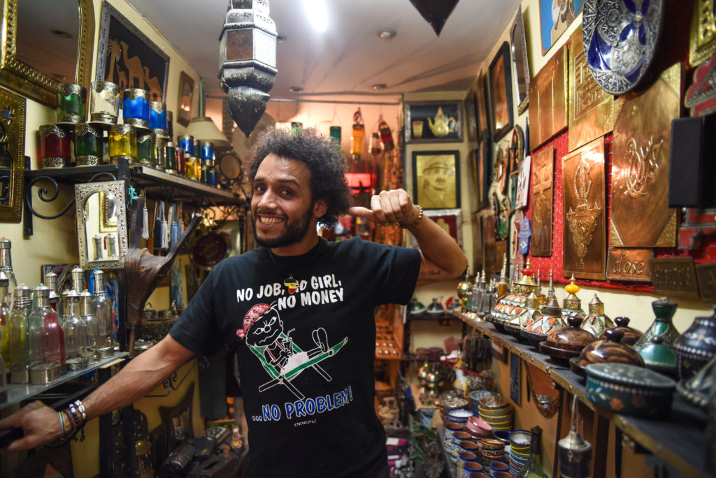 Alkhadi, 30, poses in front of his handmade metalwork art and other merchandise in his shop. Photo by Shirley Chan